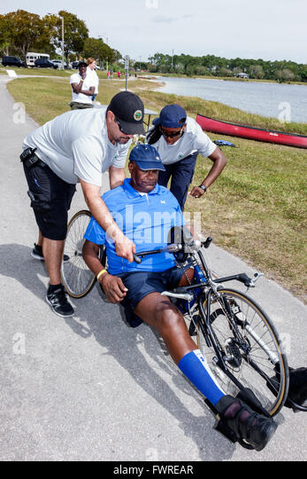 Florida FL Miami Tropical Park Paralympic Experience sports hand cycling cycle Black man disabled volunteer helping - Stock Image