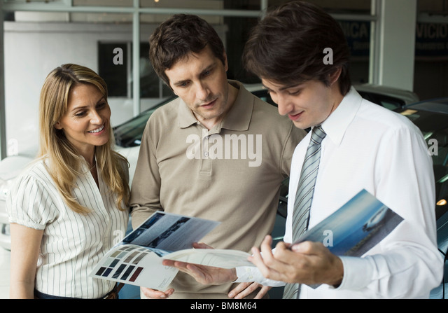 Car salesman showing couple brochure - Stock Image