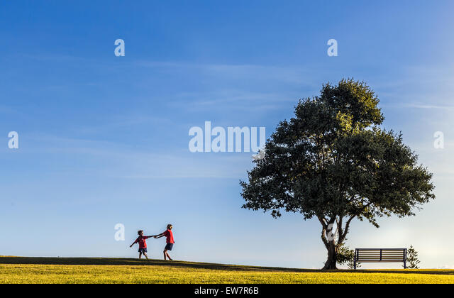 Two girls playing by a tree, Cottesloe, Perth, Australia - Stock Image