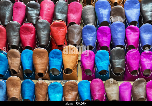 Colourful Moroccan babouches displayed on a wall shelf in a shop in Marrakesh, Morocco. - Stock Image