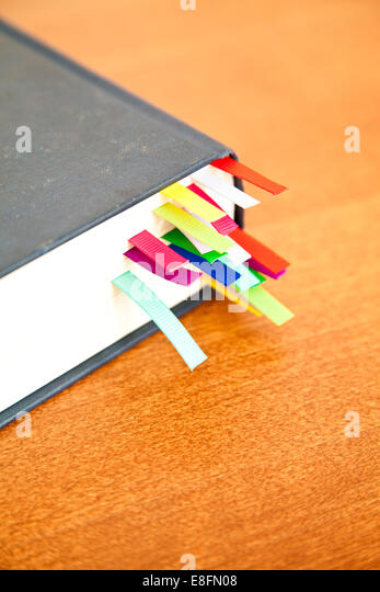 Book with multi-colored bookmarks - Stock Image
