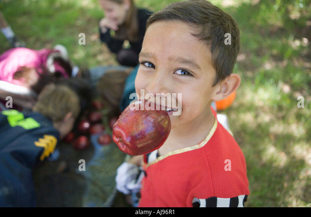 Young boy holding apple in his mouth whilst other children are bobbing for apples in background - Stock-Bilder
