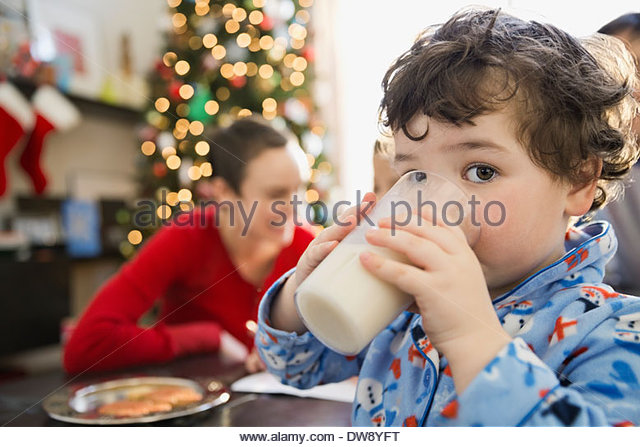 Portrait of boy drinking milk during Christmas - Stock Image