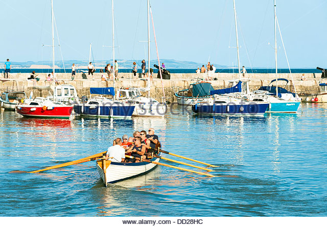 The harbour at Lyme Regis, Dorset, UK. People in a large rowing boat heading out of the harbour. - Stock Image
