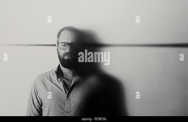 Man With Closed Eyes Standing Against White Background - Stock Image