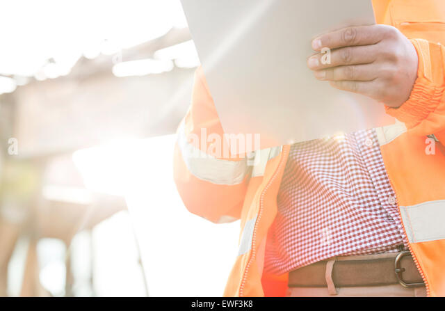 Midsection supervisor holding clipboard at construction site on sunny day - Stock-Bilder