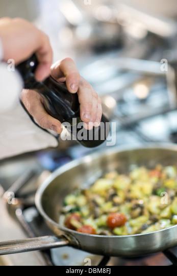 Chef Seasoning Fresh Food In Pan - Stock-Bilder