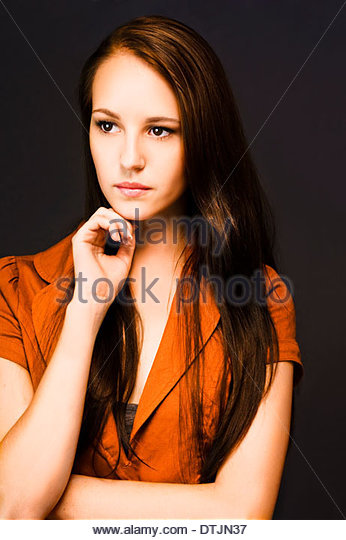 A confident young businesswoman stares thoughfully off in to the distance in a concept of a business visionary - Stock Image