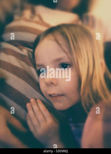 Little girl listens to mother's pregnant stomach. - Stock Image