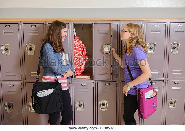 Caucasian students talking in school hallway - Stock-Bilder