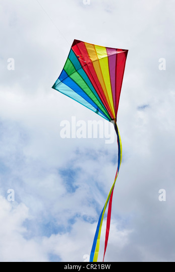 Kite flying in cloudy sky - Stock Image