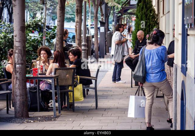 Spain Europe Spanish Madrid Salamanca Calle de Jorge Juan sidewalk cafe residents pedestrians Hispanic woman friends - Stock Image