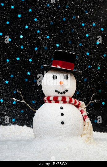 Snowman in the snow against starry night sky concept - Stock Image