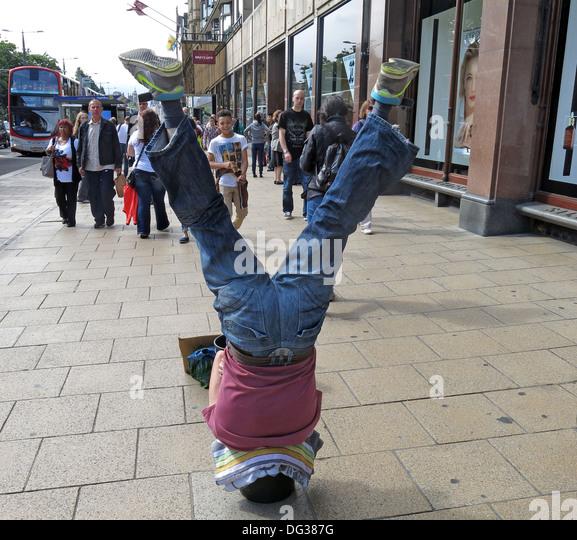 Busker in Princes st Edinburgh upside down in a bucket Scotland UK - Stock Image