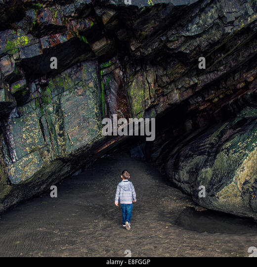 Boy standing in front of rock tunnel - Stock Image