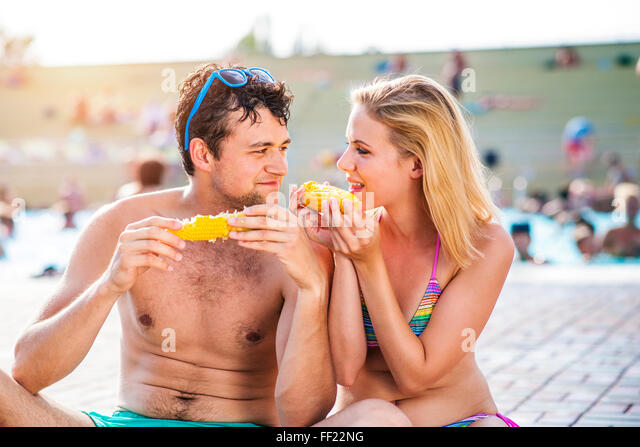 Couple in swimming suits at the pool eating corn - Stock Image