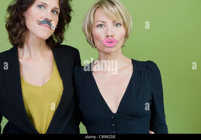Women wearing fake lips and mustache - Stock Image