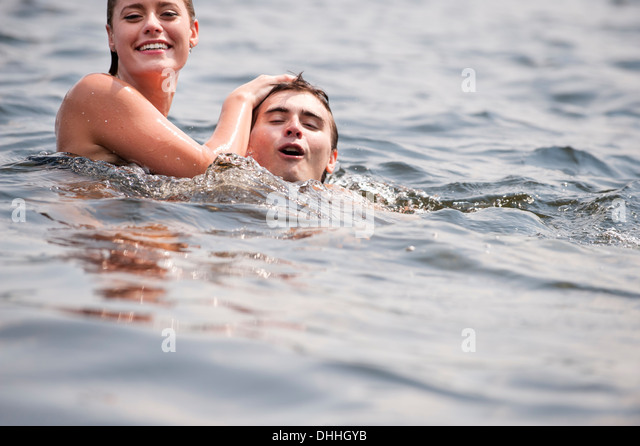 Young couple swimming in lake - Stock Image