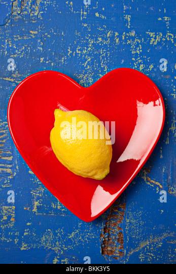 Lemon on red heart shaped plate - Stock-Bilder