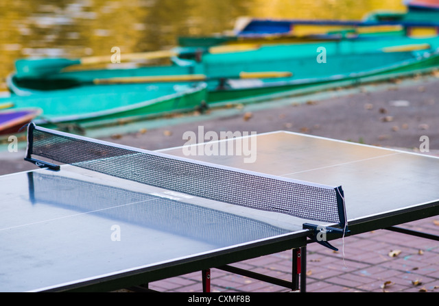 The season is over. A ping-pong table with tennis net installed on deck covered with yellow leaves - Stock Image