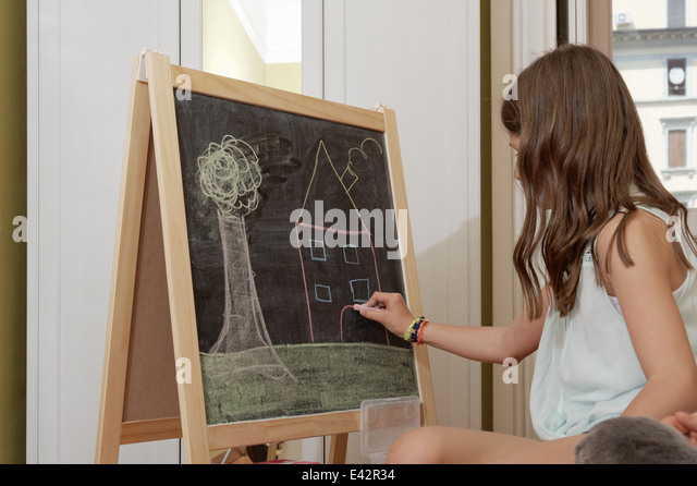 Girl drawing on blackboard - Stock-Bilder