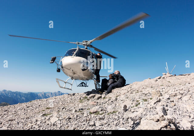 BASE jumping team exiting helicopter on top of mountain, Italian Alps, Alleghe, Belluno, Italy - Stock Image