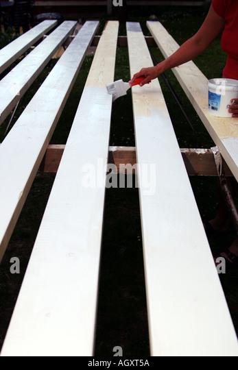 Painting white oil paint on long planks - Stock-Bilder