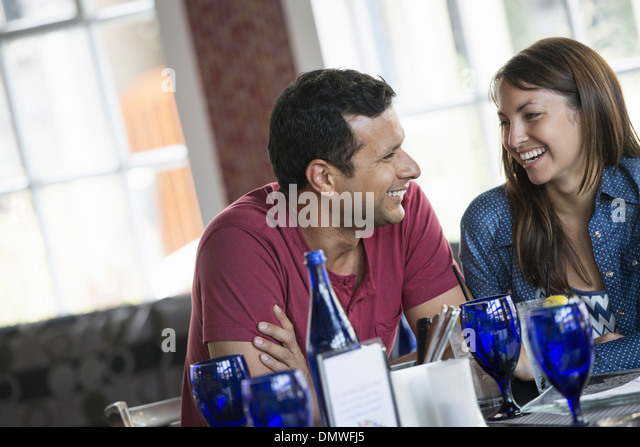 A cafe interior. A couple seated at a table. - Stock Image