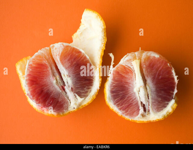 Two, opened, blood oranges on orange colored surface - Stock Image
