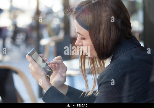 business woman using smartphone during lunch in cafe - Stock-Bilder