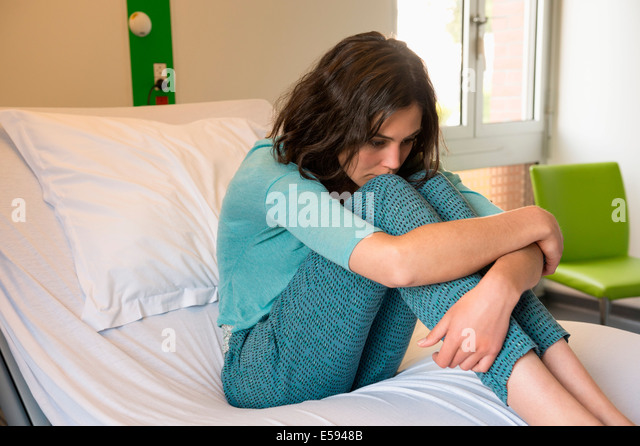 Female depressed patient sitting on the bed in a hospital ward - Stock Image