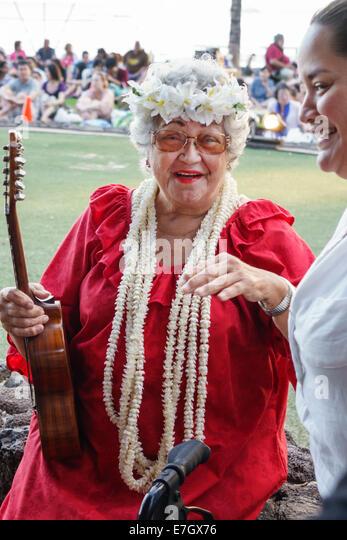 Waikiki Beach Honolulu Hawaii Hawaiian Oahu Kuhio Beach Park senior woman muumuu Hula Show entertainer ukulele wearing - Stock Image