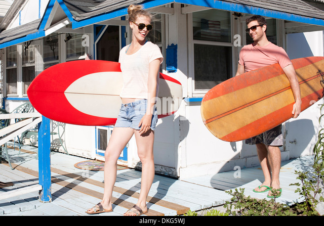 Couple on patio carrying surfboards, Breezy Point, Queens, New York, USA - Stock-Bilder