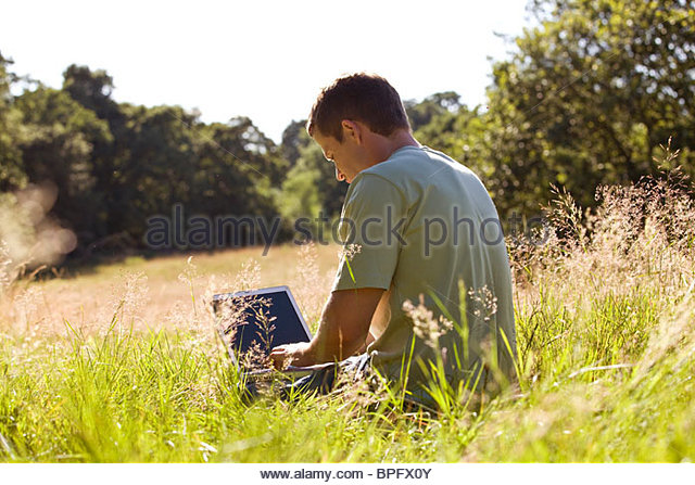 A young man sitting on the grass, using a laptop - Stock-Bilder