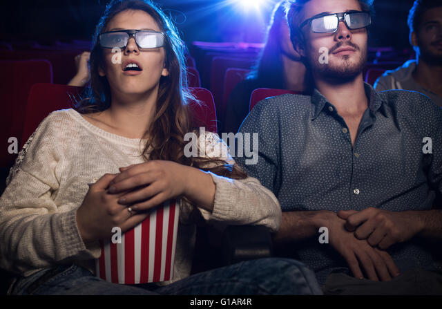 Young teenagers at the cinema wearing glasses and watching a 3d movie, a girl is eating popcorn, entertainment and - Stock-Bilder