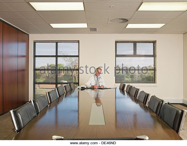 Businessman sitting in conference room with paper work - Stock Image
