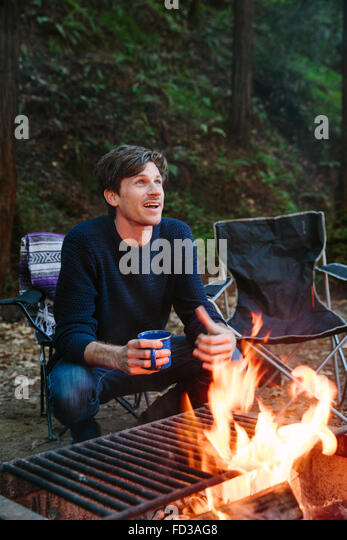 A young man sits around the campfire telling stories with friends in Big Sur, California. - Stock-Bilder