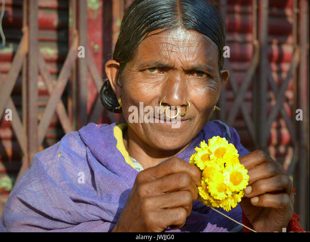 Closeup street portrait (outdoor half-length portrait, seven-eighths view) of an elderly Indian Adivasi market woman - Stock Image