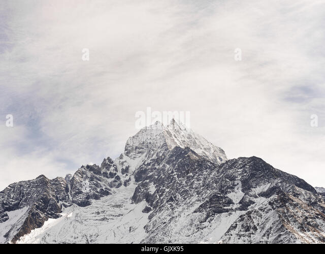 Snow covered peak of a jagged Himalayan mountain in Nepal's Everest Base Camp - Stock Image