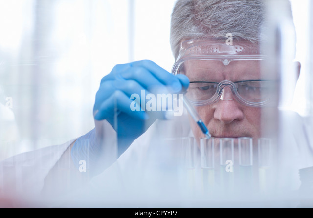 Scientist dropping liquid in test tubes - Stock Image