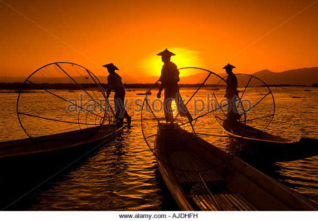 Legrower fisherman set conical traps as the setting sun reflects on Inle Lake Shan State Burma - Stock-Bilder