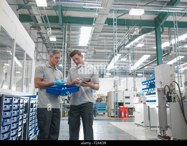 Engineers discussing work in orthopaedic factory - Stock Image