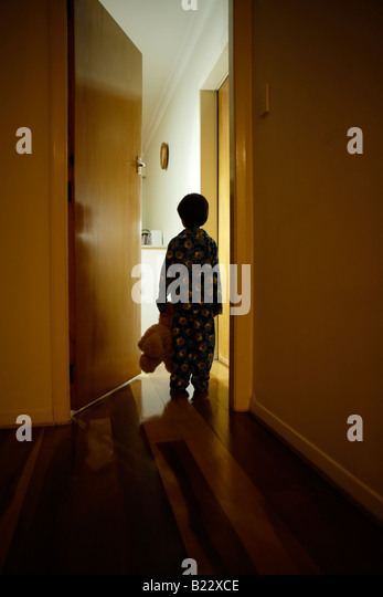 Six year old boy stands in corridor in pyjamas with teddy bear - Stock-Bilder