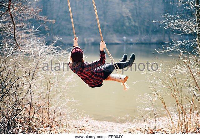 Rear View Of A Girl Swinging Against Calm Lake - Stock-Bilder