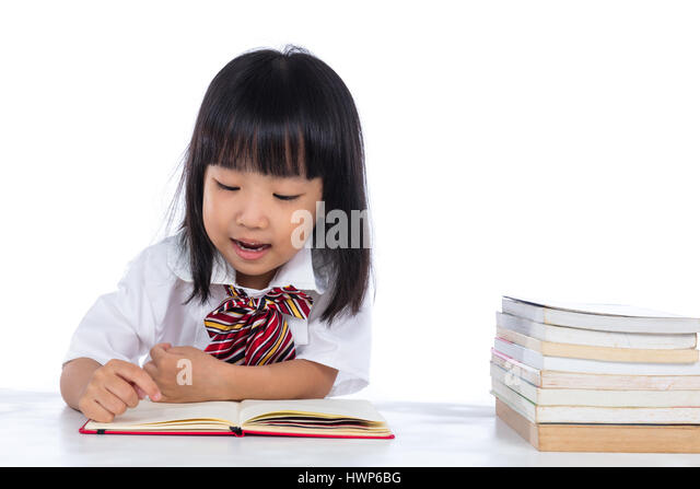 Happy Asian Chinese little girl reading book in isolated white background. - Stock Image