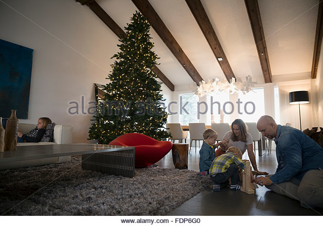 Family playing with wood blocks floor Christmas tree - Stock Image