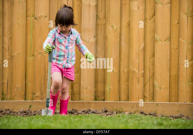 Young girl digging soil in the garden - Stock Image