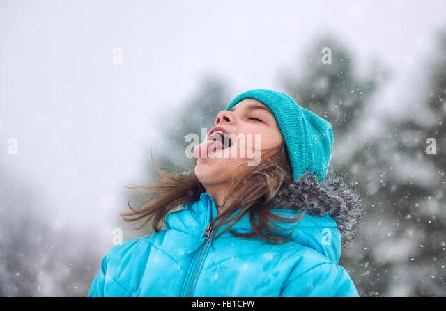 Girl looking up, sticking out tongue catching snowflakes - Stock Image