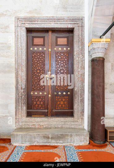 Wooden aged engraved door and marble wall, Suleymaniye Mosque, Istanbul, Turkey - Stock Image