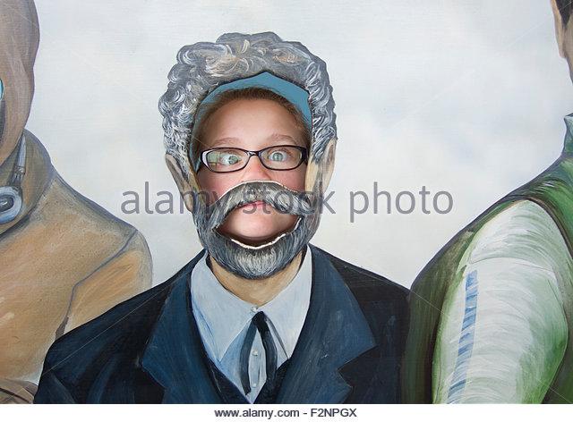 Caucasian girl posing in cutout paintings - Stock-Bilder